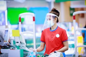 A cashier in medical protective mask and face shield working at supermarket