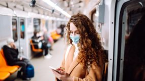 Woman in medical mask on her face with a phone in a subway