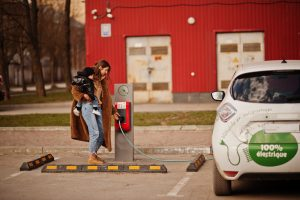 Young mother with child charging electric car at a charging station
