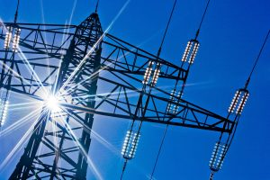 High-voltage electricity pylons against blue sky and sun rays