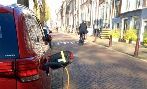 Charging electric vehicle and man riding bicycle