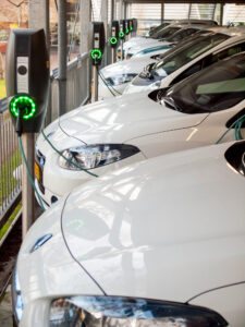 row of plug-in electric vehicles at charging stations