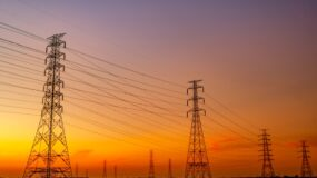 High voltage electric pylon and electrical wire with sunset sky.