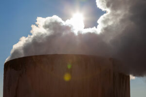 Smoke coming from the top of a chimney and blocking out the sun.