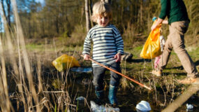 Mature father with small kids working outdoors in garden, sustainable lifestyle concept.