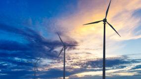 Green renewable energy concept - wind generator turbines silhouettes on sunset
